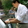 Date:   7/16/98----Garry Mauro running for Texas Governor puts a bumper sticker on Maurie Humphrey's car while going door to door off of Avalon Thursday afternoon in Longview. Kevin green