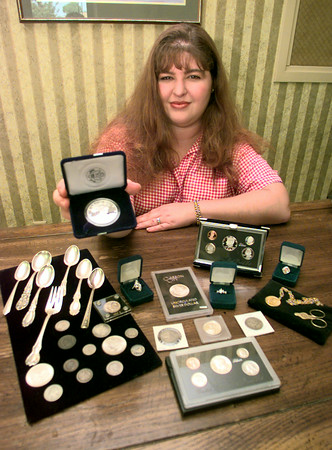 Date:   7/9/98---Julie, owner of the Coin Investor holds a US Proof Silver Eagle while other treasures lay on the desk Thursday afternoon at her store on Spur 63 in Longview. Kevin green