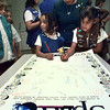 06/02/98--ShaMarla Calhoun, 5 left, and Jessica West, 7, sign their names to a poster under the gaze of ShaMarla'a mother, Deborah Calhoun, Tuesday at St. Andrew's Presbyterian Church in Longview. Scout troops from around the area are signing the poster in honor of Space Day and it will ride the Space Shuttle on Senator John Glenn's second historic space flight later this year. Matula photo.