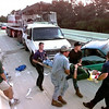 Date:   6/19/98----LFD EMT's at the head and foot of a backboard get assistance from the driver af the crane in grey and a passerby to help as they prepare to transport a worker form the white Ford van after it was rear-ended by a crane in a four vehicle accident on I-20 about 2 miles East of FM 2087 in Gregg County. Kevin green