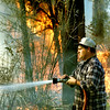 DATE--3/26/98--Lonnie Lucas with Sabine Volunteer Fire Department battles a five-acre brush fire that started on River Road Thursday afternoon in Gregg County. Firefighters from Liberty City and Kilgore joined the Texas Forest Service to extinguish the blaze. Kevin green