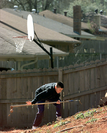 Dustin Riley, 14, spends his Spring Break Wednesday helping his dad Rodney landscape the backyard in the 3700 block of French St. in Longview. His job was to rake out the dirt and get rid of the larger rocks. Matula photo.