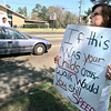 03/18/98--Angela Cole stands with a sign at the intersection of High and S. Jean Streets Wednesday trying to get motorists to slow down through the school zone for Pinewood Park Elem. LPD traffic supervisor Sgt. John Thompson talks to a driver he stopped in the street while her child waits in the passenger seat. Matula photo.