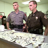 Date:   3/5/98 DPS Tooper Dale Baggett, left, and Panola County K-9 officer Kevin Lake, right, visit with a reporter while displaying $13,000, they confiscated in a drug arrest on the loop Friday afternoon in Carthage. Kevin green