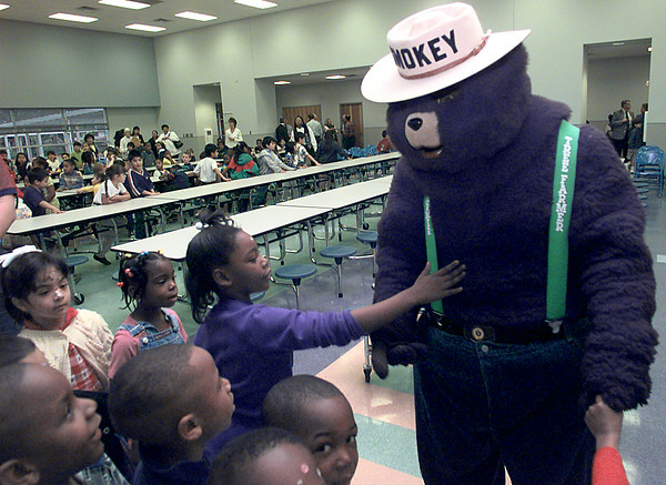 Date:   3/19/98---Lanighsa Watkin, a kindergartner, at South Ward Elementary, gives a little pat on Smokey the Bear's tummy after the Arbor Day ceremonies Thursday morning a the school in lOngview. Kevin green