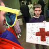 05/19/98--Lauren Kennedy, 13, plays the Red Cross blood drive mascot while looking at a poster Dillon Schaetz, 11, drew Tuesday at the Longview Red Cross open house. Dillon won a local contest with his design and it will be featured on this summer's drive's t-shirts. Matula photo.