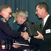 "05/12/98--LPD officer Mike Harrod, left, is given the award of ""Officer of the Year"" by the city during it's Giants of the City banquet at Maude Cobb Tuesday night. He is being handed a new sidearm by Mayor David McWhorter with police CHief Leroy Hamilton in the background. Matula photo."