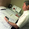 05/14/98--Bob Weidman looks over the plans to and Ore City ISD auditorium that's in the working-up stage. Weidman is a former city inspector who now uses his expertise to examine and correct architects' blueprints and designs to make sure they meet code. Matula photo.