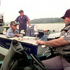 Date:   5/14/98-----Left to Right----Pete Koonce, George Koonce, center and Texas Game Warden Mike Walker, right, as he conducts a spot check Thursday morning on Lake O Pines. Kevin green