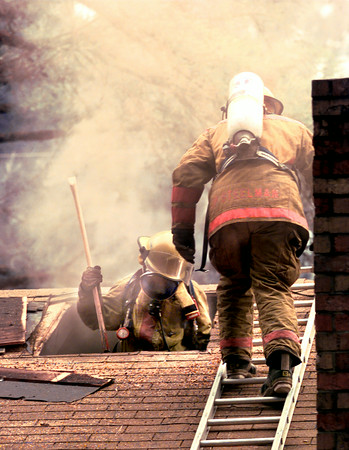 Date:   5/27/98---LFD firefighters go into the attic with an ax during a house fire in the 700 blk. of Elm St. Wednesday afternoon in Longview, no one was home at the time of the fire. Kevin green