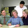 Date:   5/20/98---Left to Right---Dr Roger Johnson, left, Katy Johnson signing, Judy Johnson, right, while coach Simon Sanchez, back looks on Wednesday afternoon at Pine Tree High School in Longivew. Kevin Green