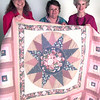 Date:   11/17/98---Lef to Right---Barbara Kenning vice chairman of community partners for children, Carol Luther with the Nite Bee of Country Patches Quilt Guild, and Betty Hunt on Rainbow room board for community partners. with quilt. Kevin green