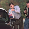 Date:   11/24/98---Charles Rader, middle, takes a donated bag of food from Brenda McIntosh at the drop-off point for donations at the annual Thanksgiving Food Drive at the Maude Cobb Convention and Activity Center. Larry Thompson, right, prepares to interview McIntosh on a live television broadcast. bahram mark sobhani