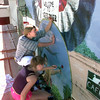 Date:   10/8/98----Gilmer High School juniors B.J. Upchurch, back, and Robin Tuel, front, paint with other students from Kelly Laminack's Art 2 and 3 class Thursday afternoon as they paint a murel on the side of the Gilmer Mirror in Gilmer for a class project. Kevin green