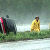 Date:   9/15/98----DPS Trooper Rodney Tandy, left, and a Texas Wrecker Service driver walks away from a car overturned in the Texas 31 median Tuesday afternoon as rains continue in Gregg County. Kevin green
