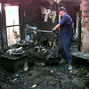 Date:   9/4/98----Gregg County asst fire marshal Clif Massingill shovels out debris after a house fire on Goforth Friday afternoon in Gregg County. Kevin green