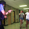 8/21/99---A Henderson PD SWAT TEAM member holds a handgun while covers students as they exit the building while a gunmen was hol-up in one of the class rooms during Saturday's drill at Henderson High School in Henderson. Kevin Green