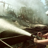 8/3/99---Josh Hollis of the Macedonia Fire Department douses a mobile home that burned Tuesday East of Longview. bahram mark sobhani