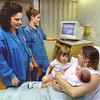 8/29/99---GSMC's labor and delivery nurse Nicole Ritter, RN, BSN, left, vists with patient Crystal Davis, right, with her two kids Taylor, left, 4, and Lauren, right, five hours old, while nurse Juli Hildreth, RN, center, watches the central monitoring system Thursday afternoon at GSMC's labor and delivery. Kevin green