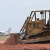 8/10/99---An airplane taxi's on the runway while a bulldozer moves dirt while the airport is under construction for a safe zone aroung the runway. Kevin green