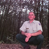 8/13/99---Texas Forest Service's Ernie Smith, is among many pine trees as he posing for a photo Friday afternoon at Lake Cherokee. Kevin green