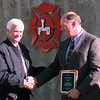 12-28-99--LFD fire chief Leon Glass, left, presents Dick Schilhab, right, general manager of the east Texas region for Transit Mix, a plaque for hte donation of materials to build the fire dept.'s smoke house in the background Tuesday morning in Longveiw. Kevin GReen