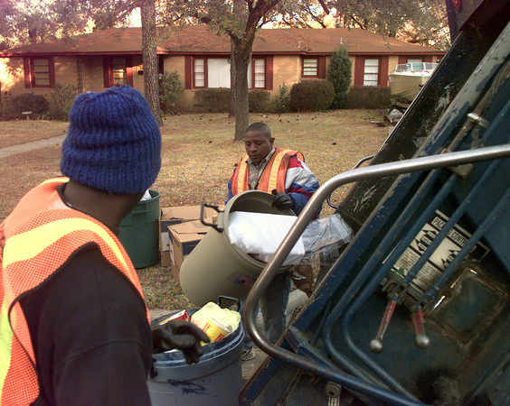 12-28-99--City of Longview trash men Michael Champion, left, and Marcus Polk, right, empties trash cans Tuesday morning on Noel St. in Longveiw. Kevin GReen
