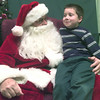 12-10-99---Taylor Vineyard,6, sits in the lap of Santa Claus played by Spring Hill State Bank customer Gene Dassonville, left, at Spring Hill State Bank Friday afternoon in Longveiw. Kevin GReen