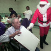 12/23/99---Emma Smith, 105, shows her surprise at receiving a gift from Ulysses Johnson, dressed as Santa, during a Christmas party Thursday at the Cleaver Memorial Convalescent Center. Gifts were given to all the residents. bahram mark sobhani