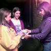 12-6-99---Heidi Dishman, left, and Julie Grotheim, center, both ninth graders at Spring Hill High School receive canned food from Spring Hill resident Joni Lewis, right, during the Fellowship of Christian Athletes door to door drive for needy families Monday night in Spring Hill. Kevin Green