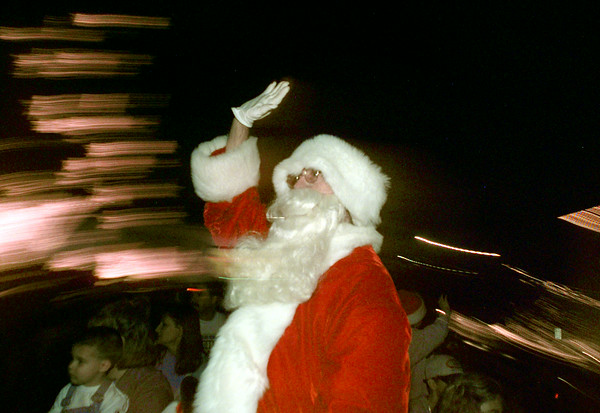 12/3/99---Santa Claus, AKA Doug Sapp of Longview, waves to the crowds as lights blur by him on top of a firetruck in the annual Christmas parade. bahram mark sobhani