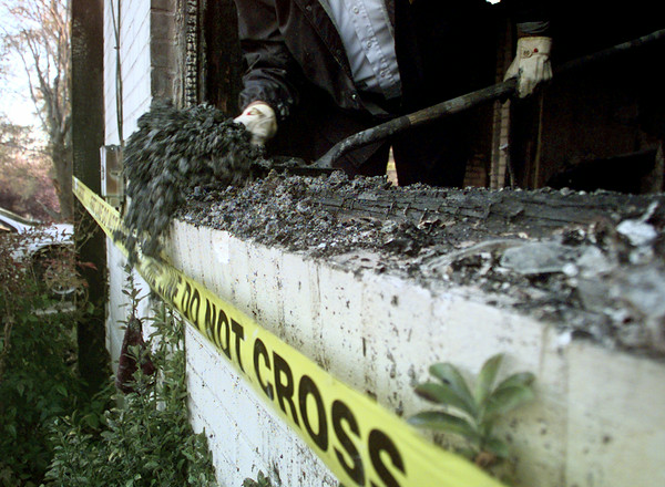 12/21/99---A Longview fire investigator sorts through the burnt rubble to find clues to a house fire in the 900 block of Wilson St. after an early morning fire Tuesday. bahram mark sobhani