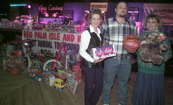 12/15/99---KYKX radio personality Dakota, left, Reo Palm Isle manager Dayton Plunkett and Community Partners boardmember Sandy Anderson show off the toys donated by Reo and KYKX to Community Partners. Most of the toys were donated during an event Dec. 10 at the Reo and other toys were brought it afterward. bahram mark sobhani