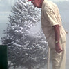 12-2-99---Jack Lewis, manager of Smotherman's Scenery on West Marshall, checks his supply of materials while flocking a Christmas tree Thursday morning in Longview. Kevin GReen
