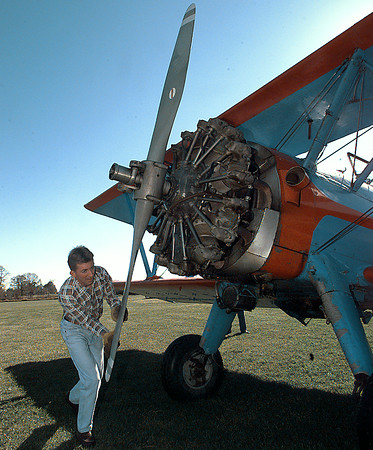 Dana Sneed pulls the prop  of his 450hp. 1942 Steerman, in order to flush exess oil from the lower cylinders  before startup for a pleasure flight in the Spring like weather at the little grass strip known as the Kilgore Air Port, Sunday afternoon. Obie LeBlanc.