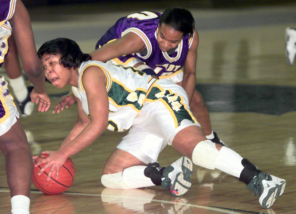 2/5/99---LHS's #12 Jennifer Mathis protects a loose ball as Lufkin's #10 battles fo rthe ball during Friday's night game at LOBO gym. Kevin green