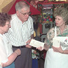 7/27/99-  Rev. William R. Cunnigham and his wife Jane, left, receive a Too Hot to Cook brochure from Longview Community Ministries volunteer, Sandra Norwood, at Papacitas Mexican Resturaunt Tuesday evening in Longview. Jessica Williamson