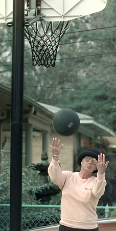 1/27/99---Lillie Snodgrass shoots baskets in her driveway Wednesday in the Pine Tree area. Snodgrass was playing basketball with her health care assistant as a daily exercise. bahram mark sobhani