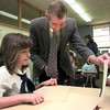 Date:   1/25/99---St Joseph's volunteer art teacher James Jenuwine of Marshall shows Brittany Gary, a third grader a sample of his work during art class Monday morning in Marshall. Kevin green