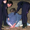 Date:   1/16/99---LPD officers prepare to transport a man early Saturday morning after a chase where the suspect hit an SGT's car then wrecked out himself. The ziplock bag on the ground looks to have weed in it. Kevin green