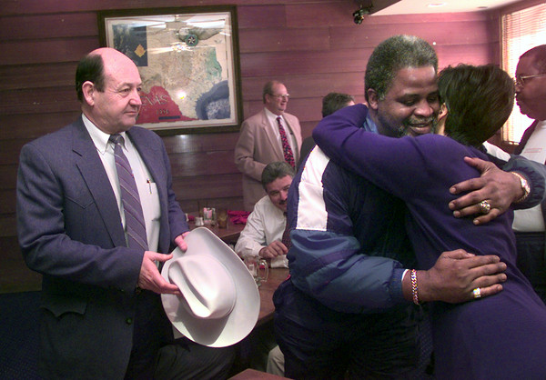 Date:   1/19/99---Gregg County Sheriff Bobby Weaver, left, looks on while Earl Campbell, center, gives Kate Finley a hug as he when in for EJ's Smokehouse Tuesday afternoon in Longview. Kevin green