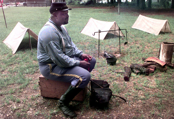 7/10/99---Ken Pollard, portrays a Texas Buffalo Soldier as he sits in camp Saturday afternoon at Martin Creek State Park. Kevin green