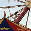 7/21/99---Jason Williams climbs up the ferris wheel Wednesday to replace some of the light coverings. Williams travels with the Stanley Shows carnival, which is part of the Northeast Texas Regional Fair, going on through July 25 at the Longview Fairgrounds. bahram mark sobhani