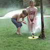 7/26/99-Ian Komer,5, left, and his cousin Tiffany Jackson, 10, try to keep cool by playing in the sprinkler in their grandmother's yard Monday afternoon in Longview.  Jessica Williamson