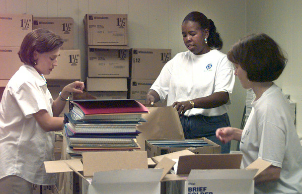7/26/99---(left to right) Julia Powers a Junior League of Longview volunteer, Shonna Vance, an employee of Buckner Children and Family Services, and Charlotte Fountain, a Junior League of Longview volunteer assemble school supply packets that will be given away in August.  Jessica Williamson