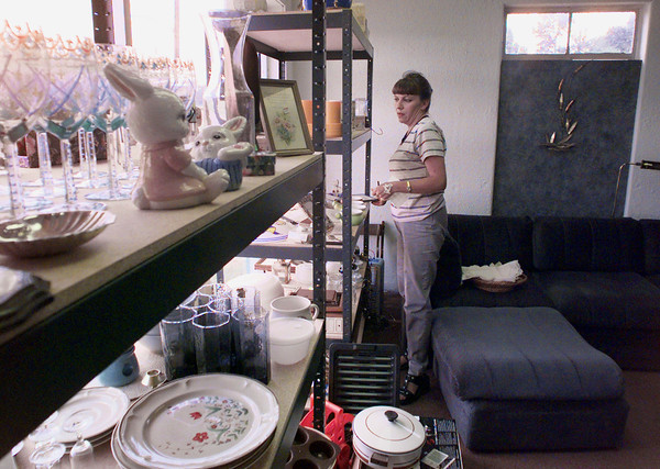 7/19/99---Nita English, assistant manager at the Women's Center Thrift Store, places items for sale on a shelf in the new store's location. The store and the Women's Center of East Texas offices, located at 2907 W. Marshall, will open today. bahram mark sobhani