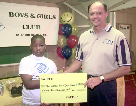 6/4/99---Nine year old kidann McGee, left, is presented with a check for the Boys and Girls Club, for 25,000 dollars by the division manager of SWEPCO Texas Keith  Honey, right, Friday afternoon at the club in Longview. Kevin green