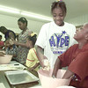 6/10/99---Deryale Woodard, 7, right, and Porsche Erwin, 12, react to the feel of kneeding dough Thursday during summer camp at Post Oak CME Church near Easton. Camp members were learning to bake bread as part of the basic life skills curriculum. bahram mark sobhani