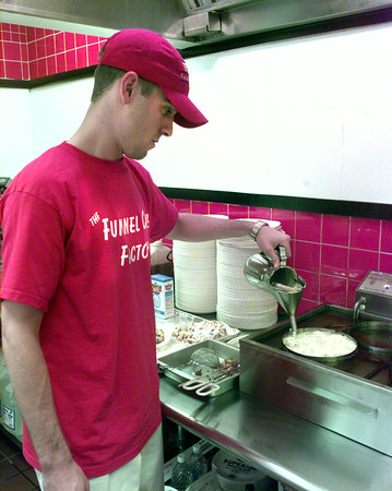 6/23/99-Shawn Hill, one of the owners of The Funnel Cake Factory in the food court at the Longview Mall, pours in batter to prepare a funnel cake. The Funnel Cake Factory offers a large variety of funnel cakes. Jessica Williamson