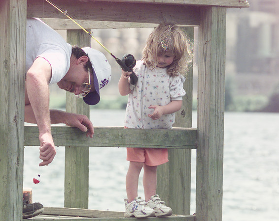 6/5/99---Rodney Vaughn of Harleton helps his daughter Heather, 2, with her line as she competes in the Kids Fishing contest at Martin Creek Lake State Park. The park held an open house Saturday, with free admission and a trail cleanup. bahram mark sobhani